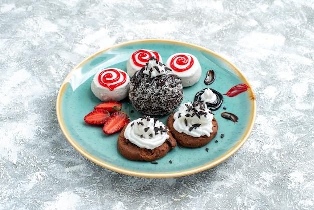 正面図甘い小さなケーキ白いスペースにさまざまな甘いビスケット