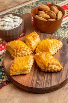 茶色のテーブルにナッツと正面図の甘いナッツペストリー