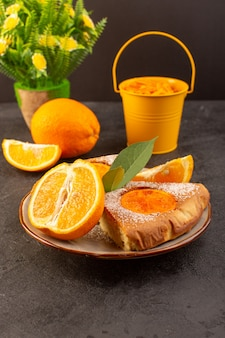 A front view sweet orange cake sweet delicious slices of cake along with sliced orange inside round plate on the grey background biscuit sweet sugar
