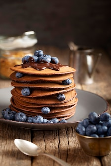 Front view sweet pancakes on plate with blueberries