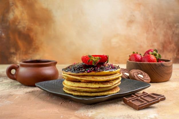나무 책상에 케이크와 쿠키와 전면보기 달콤한 팬케이크