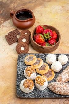 Вид спереди сладкие блины с пирожными и печеньем на деревянном столе