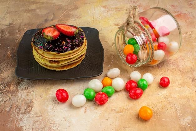 木製の机の上にカラフルなキャンディーと正面図の甘いパンケーキ