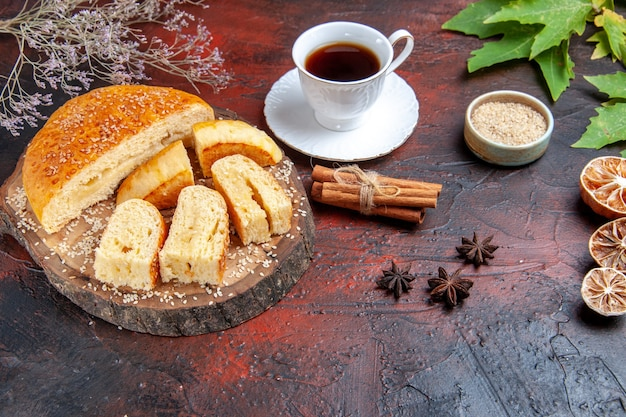 Vista frontale della pasticceria dolce tagliata a pezzi con una tazza di tè su sfondo scuro