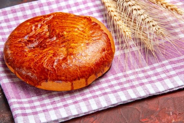 暗いテーブルの上のお茶のための正面図の甘いパイパイケーキ甘い