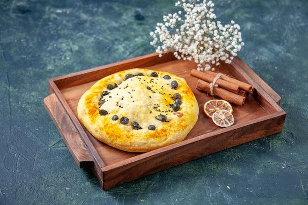 紺色の表面の木製の机の中の正面図の甘いパイ