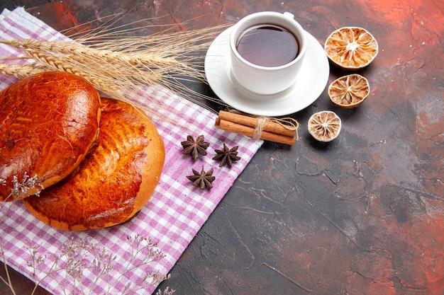 暗いテーブルケーキの甘いパイペストリーにお茶を入れた正面図の甘いパイ