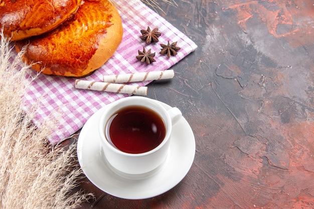 暗いテーブルの上のお茶のカップと正面図の甘いパイケーキペストリー甘い