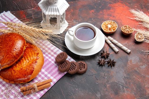 暗いテーブルの甘いパイペストリーにお茶を入れた正面図の甘いパイ