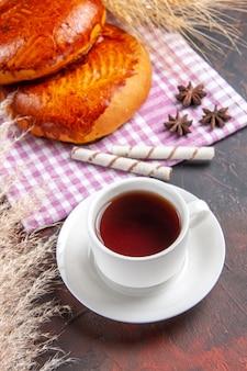 Torte dolci di vista frontale con la tazza di tè sul dolce della pasticceria della torta della torta della tavola scura