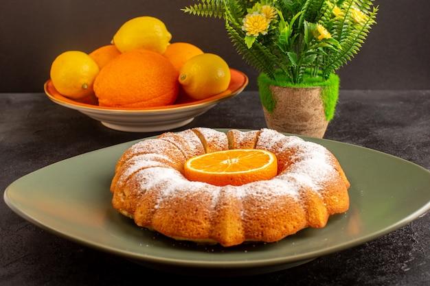 Una vista frontale dolce torta tonda con zucchero in polvere e fette deliziose dolci all'interno del piatto insieme a fiori e limoni sullo sfondo grigio biscotto zucchero biscotto
