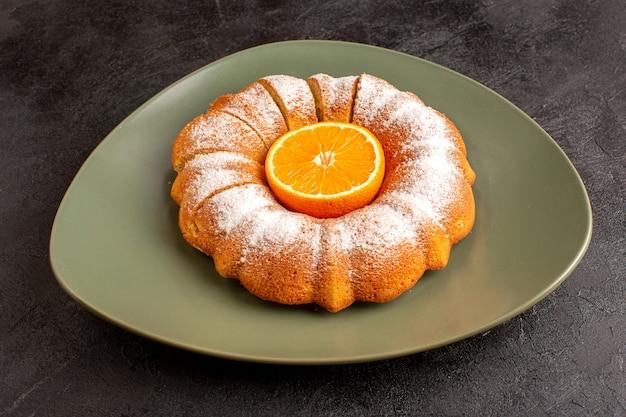 Una torta rotonda dolce vista frontale con zucchero in polvere bacchetta arancione nel mezzo affettato dolce delizioso piatto interno e sullo sfondo grigio biscotto zucchero biscotto
