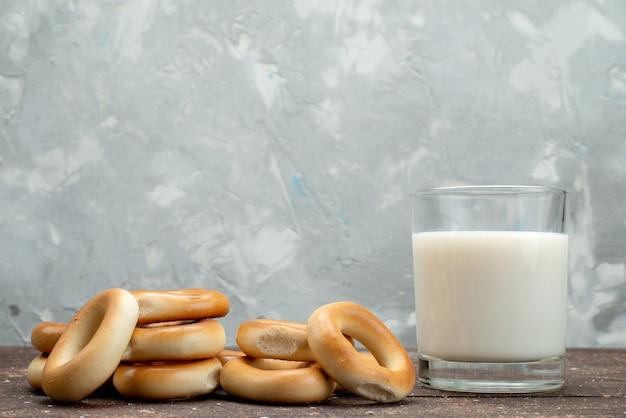 I biscotti rotondi dolci di vista frontale si asciugano con bicchiere di latte freddo su bianco, prima colazione della bevanda del biscotto del biscotto
