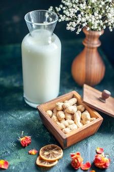 짙은 파란색 표면에 우유와 견과류가 있는 전면 보기 달콤한 맛있는 비스킷