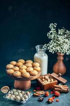 Vista frontale dolci deliziosi biscotti con latte e noci sulla superficie blu scuro