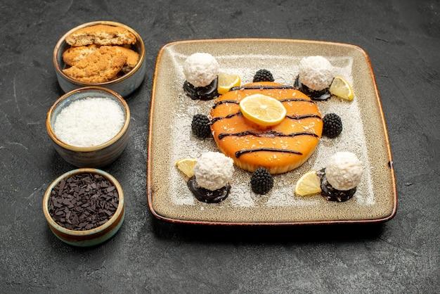 ダークグレーの背景にココナッツキャンディーと甘いおいしいパイの正面図甘いパイケーキビスケット