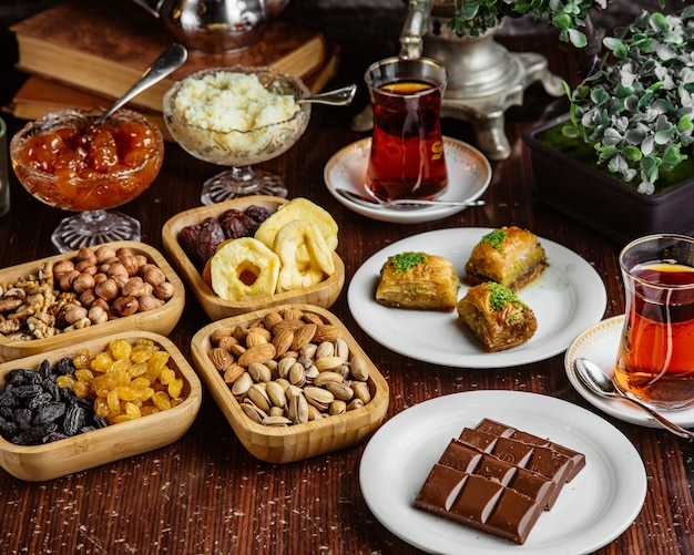 Front view sweets tea set chocolate bar pistachios dried fruits baklava with two glasses of armudu