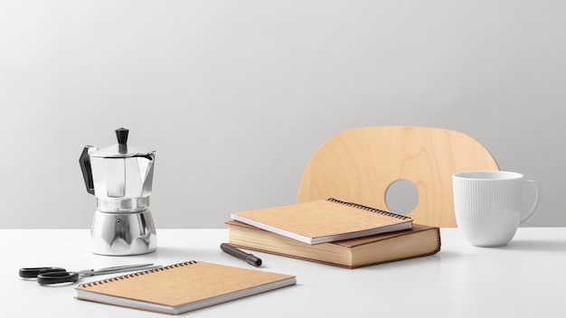 Front view of table with notebooks and kettle