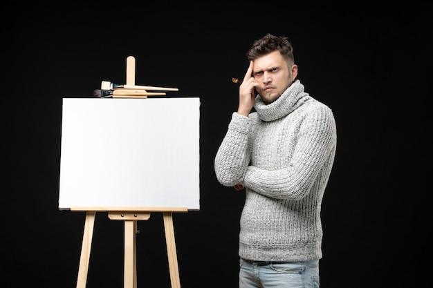Vista frontale dell'artista maschio di talento con un'espressione facciale premurosa concentrata su qualcosa sul nero