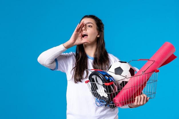 Вид спереди говорящая молодая женщина с корзиной, полной спортивных вещей