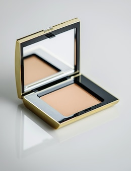 A front view tan blush box on the white desk