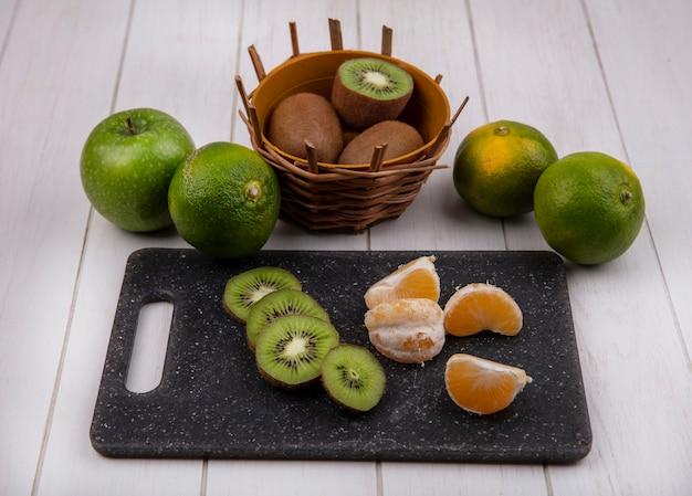 바구니에 키위와 녹색 감귤과 흰 벽에 사과와 커팅 보드에 전면보기 귤 조각