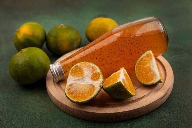 Fette di mandarino vista frontale con una bottiglia di succo su un supporto su una parete verde