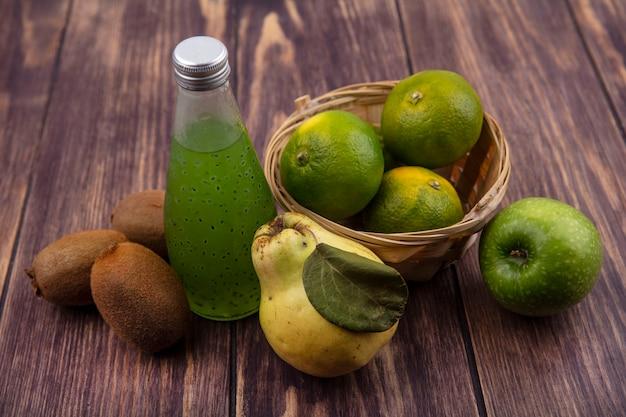 Mandarini di vista frontale in un cestino con kiwi pera e una bottiglia di succo su una parete di legno