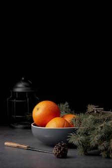 Vista frontale dei mandarini in ciotola con lo spazio della copia e del pino