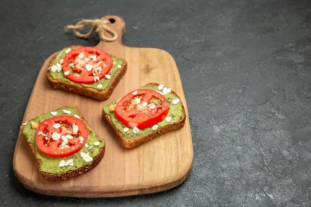 スライスした赤いトマトと正面図のおいしいアボカドサンドイッチ