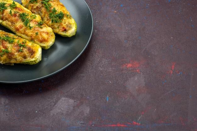 Vista frontale gustose zucche al forno con verdure all'interno della piastra sullo sfondo scuro.