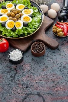 Вид спереди вкусные вареные яйца с зеленым салатом и оливками на светлом фоне