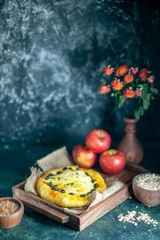 Вид спереди вкусные хлебные яблоки на прямоугольной деревянной доске, овсяные хлопья и зерна пшеницы в мисках на свободном пространстве стола