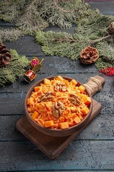 Vista frontale gustosa insalata di carote con noci su sfondo blu scuro cibo salute insalata colore dieta dado