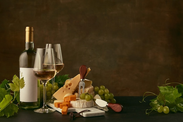 Front view of tasty cheese plate with grapes and the wine bottle, fruit and wineglasses