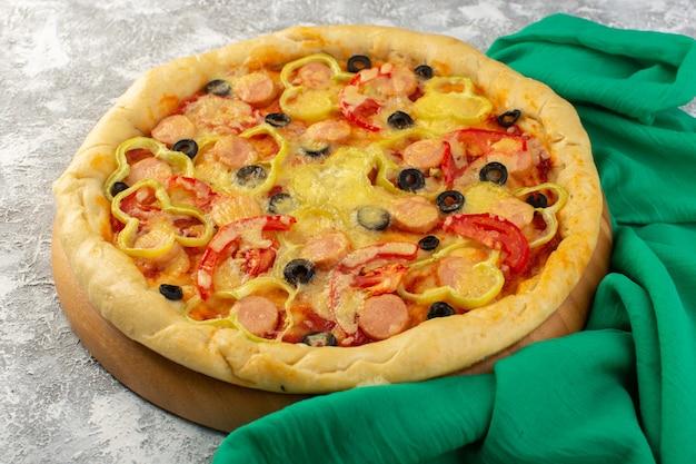 灰色の机の上のブラックオリーブソーセージと赤いトマトの正面のおいしい安っぽいピザ