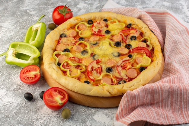 Вид спереди вкусная сырная пицца с сосисками из черных оливок и красными помидорами на сером
