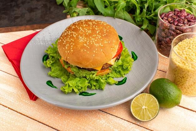 木製のクリーム色の机の上のプレートの中にグリーンサラダと野菜が入った正面図のおいしいチキンサンドイッチ。