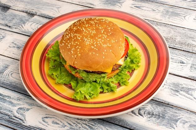 Вкусный куриный сэндвич вида спереди с зеленым салатом и овощами внутри тарелки на деревянном деревенском сером столе.