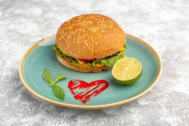 白い机の上にレモンとプレートの中にグリーンサラダと野菜を添えた正面図のおいしいチキンサンドイッチ。
