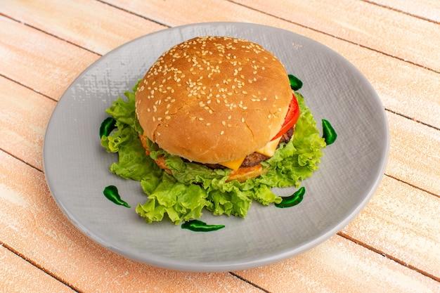 Vista frontale gustoso panino al pollo con insalata verde e verdure all'interno del piatto sul pavimento in legno panna hamburger fast food panino hamburger