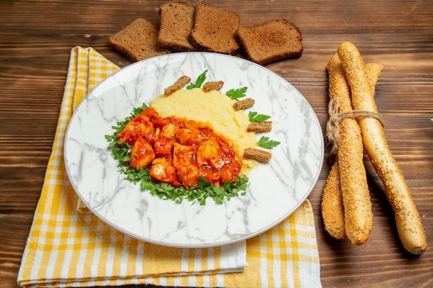 茶色の机の肉料理ディナー ポテトの食事にマッシュ ポテトとパンを添えたおいしいチキン スライスの正面図