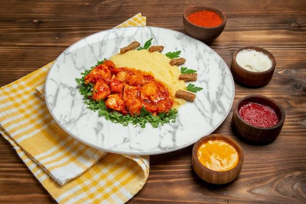 茶色の机の肉料理ディナー ポテトの食事にマッシュ ポテトと調味料を添えたおいしいチキン スライスの正面図
