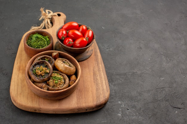Вид спереди вкусные приготовленные грибы с помидорами и зеленью на темном столе из диких спелых продуктов