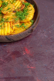 Vista frontale gustose patate cotte con verdure all'interno di un piatto marrone sulla superficie scura che cucina patatine fritte cibo cena