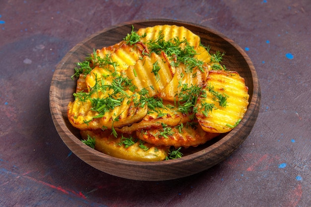 Vista frontale gustose patate cotte con verdure all'interno del piatto sulla superficie scura cucinando patatine fritte cibo cena