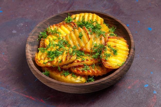 Вид спереди вкусный приготовленный картофель с зеленью внутри тарелки на темной поверхности, чипсы для приготовления ужина, еда, картофель