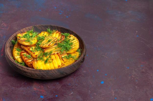 正面図暗い表面のプレートの内側に緑が付いたおいしい調理済みジャガイモ調理用シプディナーフードポテト