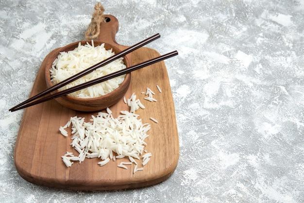 Vista frontale gustoso riso cotto all'interno di un piatto marrone con bastoncini su spazio bianco