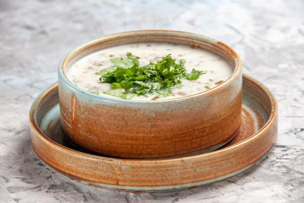 正面図ライトホワイトのテーブルミルクスープの緑の皿に緑のおいしいdovgaヨーグルトスープ